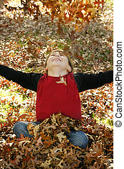 Autumn Joy - A boy throws a pile of leaves overhead and...