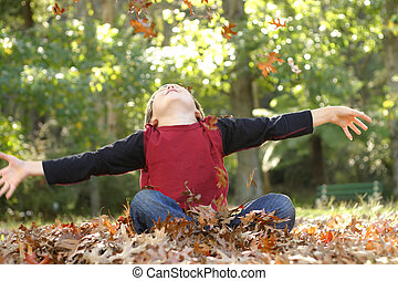 Boy with outstretched arms - A boy throws fallen leaves up...