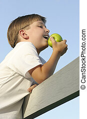 Children: Health and Nutrition - Boy on a fence eating a...