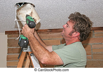 Electrician Removing Light - an electrician removing an...
