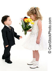 Boy Surprising Girl - Toddler boy in suit giving flowers to...