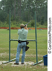 Skeet Shooter - A skeet shooter fires his shotgun as the...