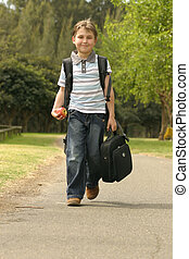 Back to School - Boy walking to school. He has a backpack,...