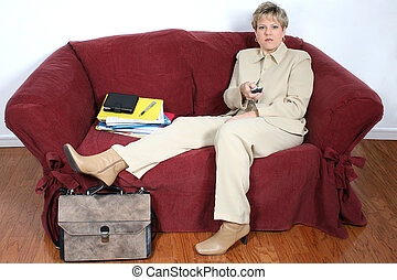 Taking A Break - Woman in beige suit with remote, sitting on...