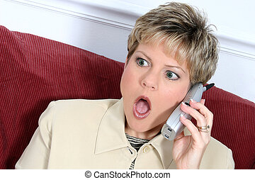 Woman Shock Phone - Woman in beige suit speaking on cordless...