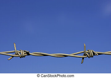 barbed wire fence - Detail of barbed wire fence against a...