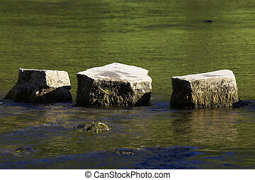 3 stepping stones in river