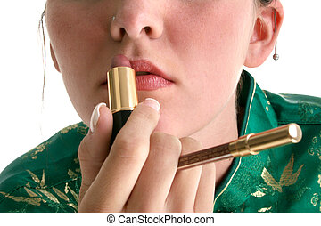 Lips Makeup Lipstick - Teen girl putting on lipstick Holding...