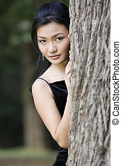 Outdoor Model 18 - A beautiful asian woman peeks out from...