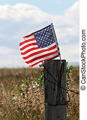rural america - american flag, battered and torn, flies...