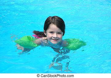 Fun In the Pool - Five year old girl swimming in a pool
