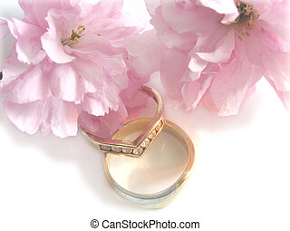 wedding bands and flowers over a white background