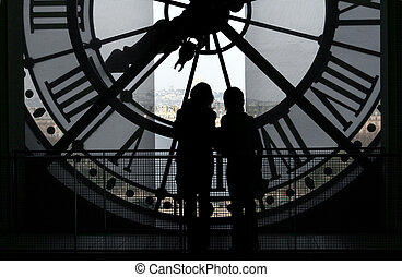 Clock @ Orsay Museum - 2 silhoettes against the clock at the...
