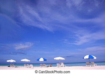 Beach Parasols - Row of parasols on white sand beach