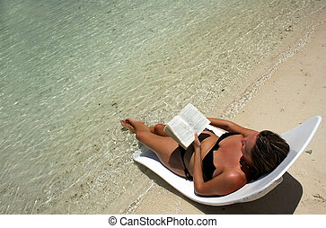Relaxing Read - Girl on lounger reading by tropical sea