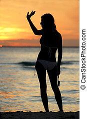 Sunset Goodbye - Girl in bikini waving goodbye at sunset
