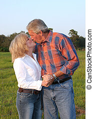 Romantic Kiss - a good looking mature couple kissing in the...