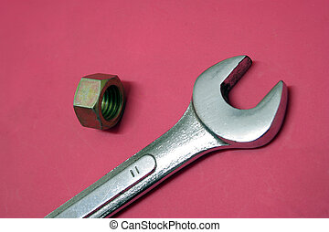 Spanner and Nut on a dark pink background