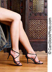 legs 3 - Beautiful, long legs with black sandals on a wooden...
