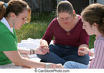 Teen Prayer Circle 2 - Three teen girls gathered outdoors to...