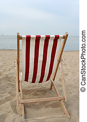 Beach chair - An empty redwhite wooden beach chair at the...