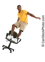 Chair Surfing Humor - Young man chair surfing Shot in studio...