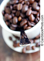 Coffe Cup - Coffe beans in cup with teaspoon; focus is on...