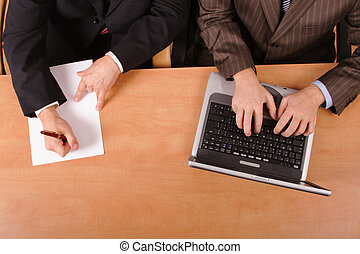 working together - Men working at the desk in the office.one...