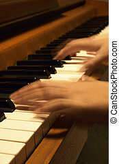 Playing The Piano - A musicians hands in blur-motion while...