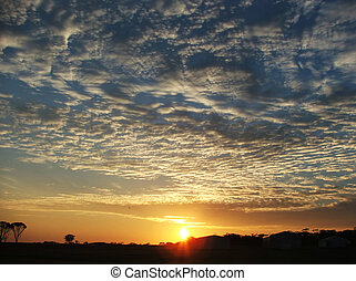 Sunsrise sky over farm - The early morning sun rises in the...