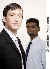 Businessmen 9 - A businessman looks confident (in focus)....