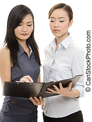 Signing The Contract - Two asian businesswomen sign a...