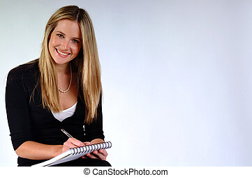 Girl Taking Notes - Young woman sitting ready to take notes.