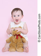 girl smiling and playing with teddy bear