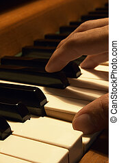 Playing The Piano - A close-up of a mans hand on the piano...