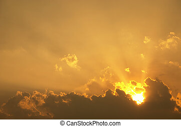 Sunrise & Sunsets - Sun rays shining from behind some clouds
