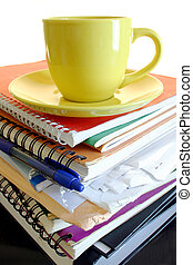 Workload - Coffee cup on pile of files