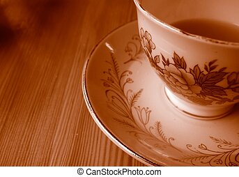 Teacup and saucer - Teacup with tea and saucer on wood table