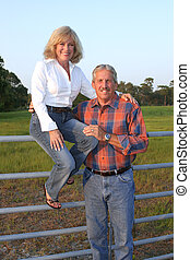 On The Fence - A good looking mature couple on a farm The...