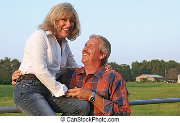 Sharing A Joke - A good looking mature couple on the farm,...