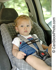 Car Seat Safety - Baby boy in a car seat for safety Focus =...