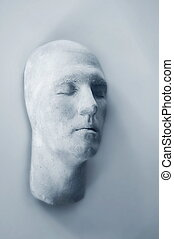 Face - plaster maskface hanging on wall - abstract alone