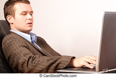 man with laptop - young smart casual business man working on...