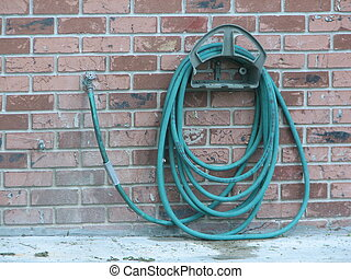 Garden Hose - Shot of a green garden hose hanging in a...