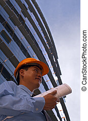 Architect - An asian male in a hard-hat holding some floor...