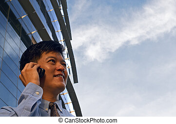 A Business Call - An asian businessman talking on the...