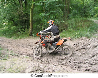 Dirt Bike - A man riding a motorbike through some thick mud.