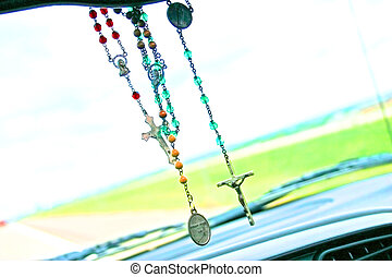 dash board Jesus - rosaries hanging from a rearview mirror