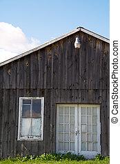 Ramshackle - A run-down old farmhouse against a blue sky.