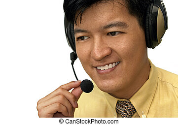 How May I Help You - Asian male adjusting headset while on...